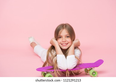 Relax and fun. Happy childhood. Kid girl relax lean penny board. Modern youth hobby. Girlish leisure concept. Girl happy face lay on penny board pink background. Originally designed girls skateboard.
