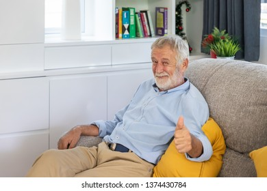 Relax happy senior old man eldery sitting on comfortable sofa in living room thumb up looking camera