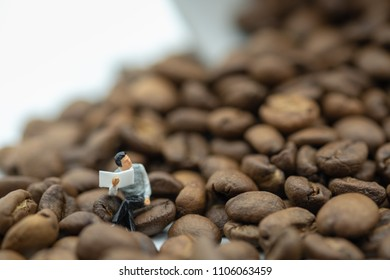 Relax, hobby and business concept. Businessman miniature figure sitting and reading a newspaper on coffee bean with white cup of coffee