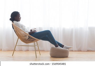 Relax at home. African american girl resting in wicker armchair and drinking coffee against window, free space