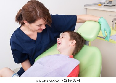 Relax kid laughing in dentist chair and having fun with friendly payful doctor
