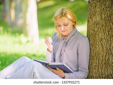 Relax leisure an hobby concept. Best self help books for women. Books every girl should read. Girl concentrated sit park lean tree trunk read book. Reading inspiring books. Bestseller top list.