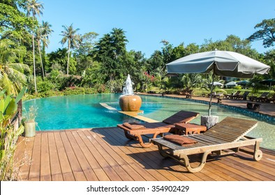Relax in The Luxury Hotel on The Island of Thailand. Couple of Wooden Chair on Terrace under The Umbrella by The Beautiful Luxury Swimming Pool surrounded by Various Type of Palm Trees in The Garden.