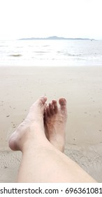 Relax of man feet above the wet beach point to the sea view