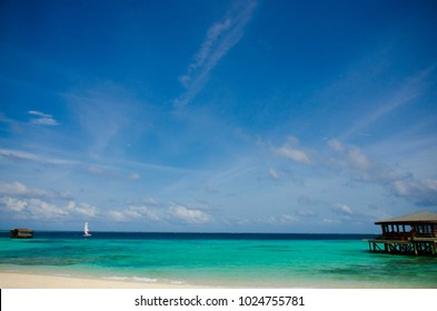 Relax on the maldives beach seeing sailboat in blue sea and blue sky and water villa