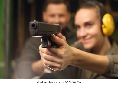 Relax on the shooting, a woman shot with a Glock. Woman takes lessons in shooting with a handgun on the shooting range