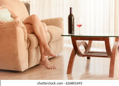 Relax on your day off concept. Woman relaxing at home with a glass of wine.