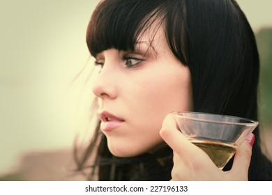 Relax outside. Young women face side view and glass of wine close up. Focus on glass.