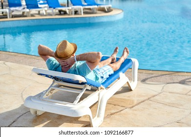 Relax in the pool summer. Young and successful man in hat lying on a sun lounger at the hotel on the background of sunset, concept time to travel.