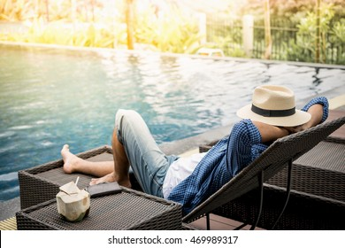 Relax in the pool. Young and successful man lying on a sun lounger at the hotel on the background of sunset.