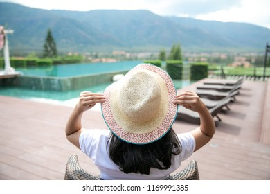 Relax in the pool. Young woman lying on a sun lounger at the hotel on the background of mountain view