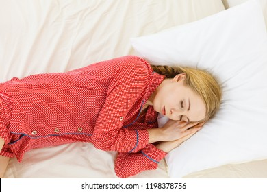 Relax rest sleep positions concept. Girl drowning in dreams. Young woman wearing red dotted pajamas lying in bed on the side dreaming deeply.