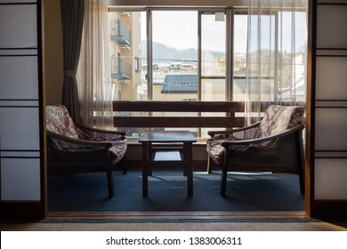 Relax seats near windows in tatami room of traditional ryokan hotel with Shibu onsen town background, Yamanouchi, Nagano, Japan. Travel destination for snow monkey park, ski, and hot spring.