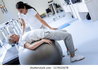 Relax. Smart friendly professional doctor looking attentively at her aged patient while persuading him to relax on a big comfortable fitball