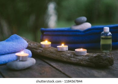 Relax spa concept with burning candles, stones, towels and aroma oil. Old wooden background