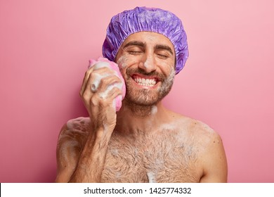 Relax, spa, hygiene, softness concept. Joyful smiling young man with broad smile, shows white perfect teeth, rubs cheek with sponge, has foam on body, takes shower, poses against pink background