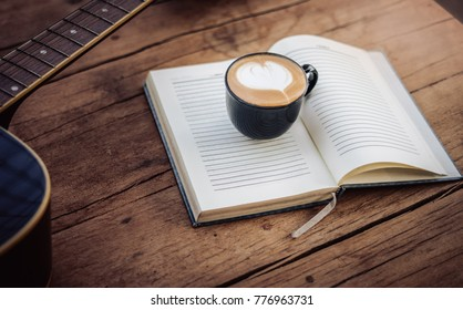 Relax time with coffee,Latte art with book phone and guitar on wood table