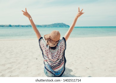 Relax time on summer or holiday concept. Back side view of the Asian girl backpack in straw hat relaxing on the beach and looking forward into the sea. Travelling in Asia.
