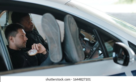 Relax time two policemen eating donut use phone smile talk sitting in patrol car help happy african american break rest gangster uniform funny teamwork portrait slow motion