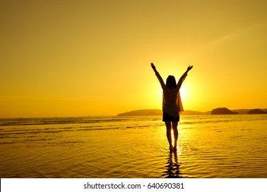 Relax Woman jumping sea on the beach   Sunset silhouette,Happy Vacation Holiday Concept.