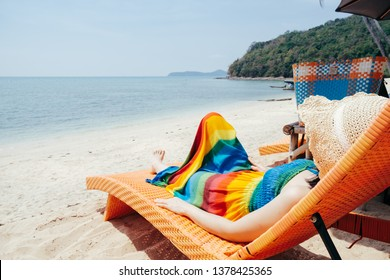 Relax Woman on  Lounger  on  the beach and clouds  sky.Summer holiday concept.