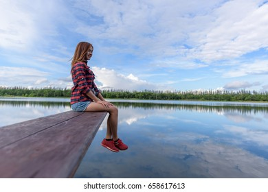 Relax with a woman sitting on the view and nature on the waterfront.