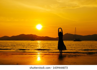 Relax Woman standing  on the beach  sea  Sunset silhouette,Happy Vacation Holiday Concept.