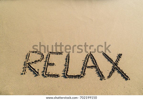 Relax word on sand, beach concept