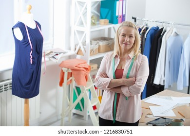 Relaxation after successful work. Unusual foreshortening from the top. Beautiful European woman looking at the camera, standing near the table in the workshop with clothes hanging in the background
