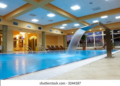 Relaxation Area with swimming pool, artificial waterfalls and wooden chairs