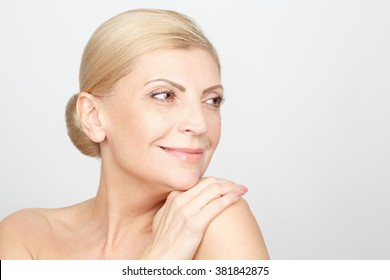 Relaxation is a beauty secret. Studio closeup of a gorgeous cheerful mid adult woman smiling looking away warmly with her hand on her shoulder