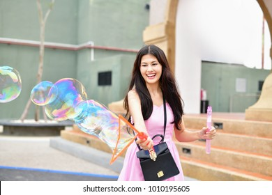 Relaxation concept. Asian girls are playing bubbles with fun. Beautiful girl relaxing on the beach. Beautiful girls like to do activities and play bubbles at the beach.