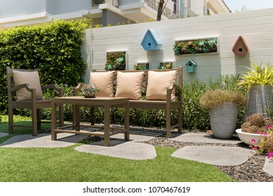 A relaxation corner, With brown wood table and a chairs set with pillows in small garden.