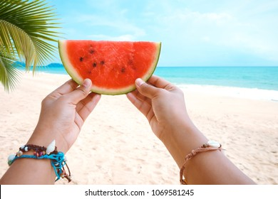 Relaxation and Leisure in Summer - Lifestyle of tanned woman holding a watermelon, On hands many seashell bracelets. Tropical island beach. Summer vacation concept.