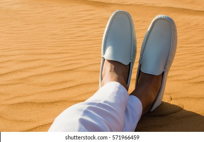 Relaxation. Mans legs/feet lying on the hot desert sand.