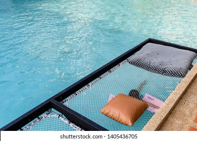 Relaxation mesh seat with pillows jut out on swimming pool