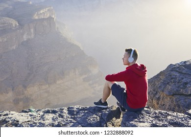 Relaxation in mountains. Young man with headphones sitting on the edge of cliff and listening music.