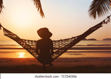 relaxation on the beach, woman in hammock enjoying beautiful tropical sunset