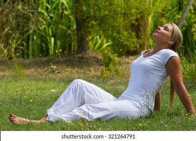 relaxation outdoors - happy young woman enjoying sun and vacation resting on grass, closing eyes with green surrounding, profile view, summer daylight