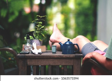 Relaxation scene of hot teapot and teacup with gardening tools and smartphone put on table.Happy man in casual dress relax on a chair and laying his legs on the table after finish renovate gardening.