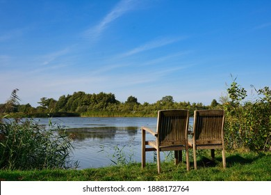 relaxation scenery, two chairs invites to take a rest next to pond at summer and blue sky