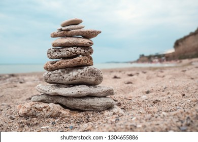 Relaxation at sea in countries with cold climates. Stack of stones on beach, nature background. Stone cairn on ocean blurry background. Concept balance and freedom, symbolizing stability, zen, harmony