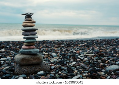 relaxation at sea. Stack of stones on beach - nature background. Stone cairn on green blurry background, pebbles and stones. Concept balance