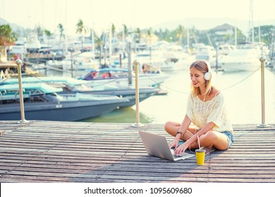Relaxation and technology. Pretty young woman using laptop computer sitting on embankment deck.