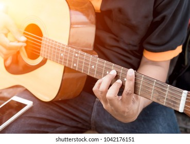 Relaxation time,Happy man playing the guitar while sitting on chair ,Practicing in playing guitar,Handsome young men playing guitar