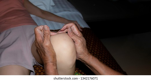 Relaxation woman with traditional massaging knee by professional while enjoy the acupressure techniques.Female physiotherapist giving knee massage to woman.Body care treatment by Thai massage
