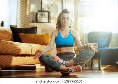 relaxed active woman in sport clothes in the modern living room meditating using balance board.