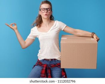 relaxed active woman in white shirt with a cardboard box doing yoga isolated on blue