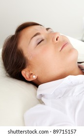 Relaxed acupuncture patient with eyes closed, undergoing a facial beauty treatment
