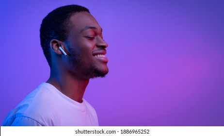 Relaxed African American Man Listening Music In Wireless Airpods Earphones In Neon Light, Smiling Black Guy Wearing Bluetooth Earpods Enjoying Favorite Songs Over Purple Background, Panorama